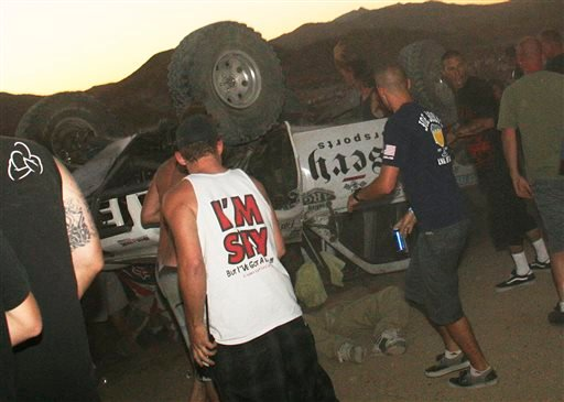 In this Aug. 14, 2013 file photo, bystanders rush to help a victim, center, pinned under an overturned off-road race truck moments after it plowed into a crowd after sailing off a jump at the California 200 off-road race in Lucerne Valley Calif.