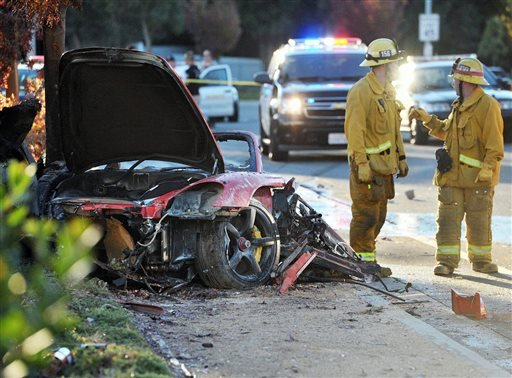 In this Nov. 30, 2013 file photo, firefighters stand near the wreckage of a Porsche that hit a light pole and burned on Hercules Street near Kelly Johnson Parkway in Valencia, Calif., a crash that killed actor Paul Walker and his friend Roger Rodas.
