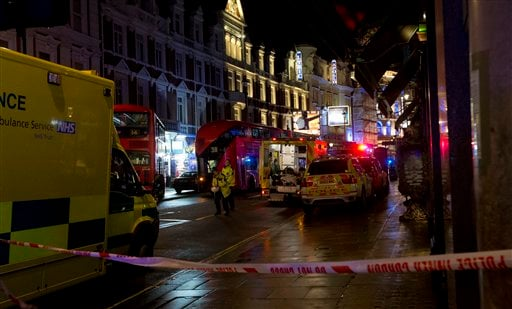 Emergency service vehicles gathered among London buses following an incident during a performance at the Apollo Theatre, far right, in London's Shaftesbury Avenue, Thursday evening, Dec. 19, 2013. (AP)