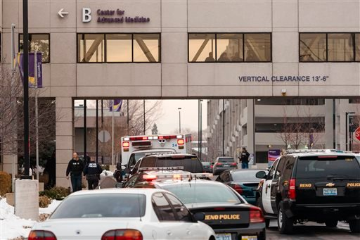 Officers gather in front of the Renown Regional Medical Center after a lone gunman shot and injured four people before killing himself , Tuesday, Dec. 17, 2013 in Reno, Nev. (AP Photo/Scott Sady)
