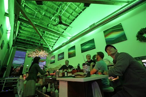 Lightbar patrons sit in a green glow from special lights in Portland, Ore., Thursday, Dec. 19, 2013.