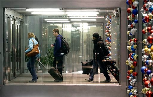 Passengers walk through Terminal 3 at O'Hare International Airport in Chicago on Saturday, Dec. 21, 2013.