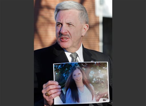 In this Saturday, Dec. 14, 2013, file photo, Arapahoe County Sheriff Grayson Robinson holds a picture of Claire Davis, the 17-year-old student who was shot in the head by a classmate, during a briefing at Arapahoe High School in Centennial, Colo.
