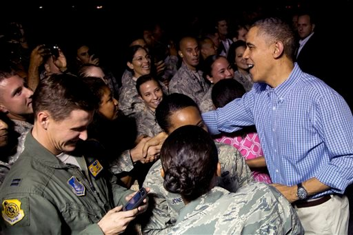 President Barack Obama greets members of the military on the tarmac as he arrives with the first family on Air Force One at Joint Base Pearl Harbor-Hickam, in Honolulu, Friday, Dec. 20, 2013.