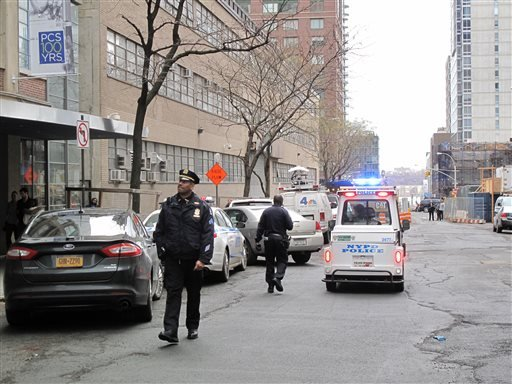 In this Sunday, Dec. 22, 2013 photo, New York Police Department officers police walk in front of a high-rise apartment building where they said a 35-year-old man and a 3-year-old child died after plummeting from the building in New York.