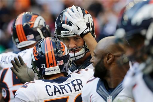 Denver Broncos' Peyton Manning, center, celebrates with teammates after he threw a touchdown pass against the Houston Texans during the third quarter of an NFL football game on Sunday, Dec. 22, 2013, in Houston.