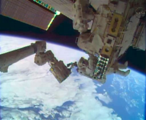 In this image taken from video provided by NASA, astronauts Rick Mastracchio, top, and Michael Hopkins work to repair an external cooling line on the International Space Station on Monday, Dec. 24, 2013, 260 miles above Earth.
