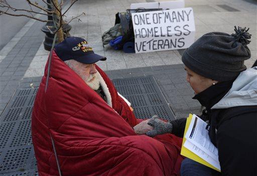 In this Wednesday, Nov. 20, 2013 photo, homeless Korean War veteran Thomas Moore, 79, left, speaks with Boston Health Care for the Homeless street team outreach coordinator Romeena Lee on a sidewalk in Boston.