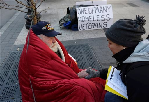 In this Wednesday, Nov. 20, 2013 photo, homeless Korean War veteran Thomas Moore, 79, left, speaks with Boston Health Care for the Homeless street team outreach coordinator Romeena Lee on a sidewalk in Boston.