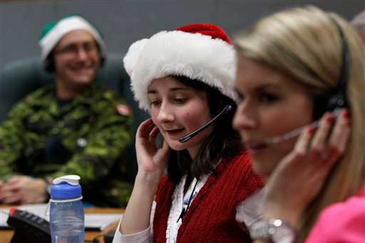 In this Dec. 24, 2012 file photo, volunteer Katherine Beaupre takes phone calls from children asking where Santa is and when he will deliver presents to their house,during the annual NORAD Tracks Santa Operation.