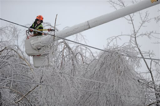 Andrew Powers, an arborist with Asplundh Tree Experts, clears iced branches from power lines along Mayflower Heights Drive in Waterville, Maine, on Monday, Dec. 23, 2013. (AP Photo/Morning Sentinel, Michael G. Seamans)
