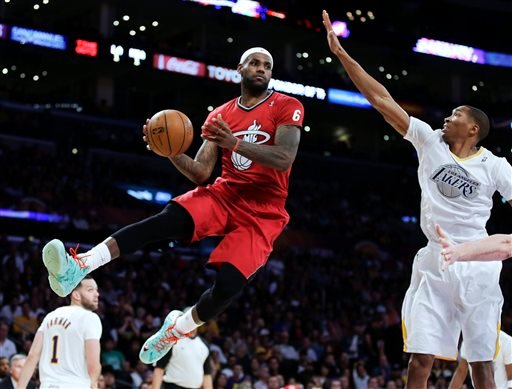 Miami Heat forward LeBron James, left, passes around Los Angeles Lakers guard Wesley Johnson during the second half of an NBA basketball game in Los Angeles, Wednesday, Dec. 25, 2013. (AP Photo/Chris Carlson)