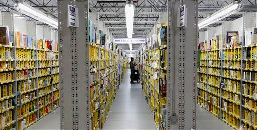 "FILE - In this Monday, Dec. 2, 2013, file photo, an Amazon.com employee stocks a shelf at an Amazon.com Fulfillment Center on ""Cyber Monday"". shoppers waited until the last possible minute to buy presents this year, even online. (AP)"