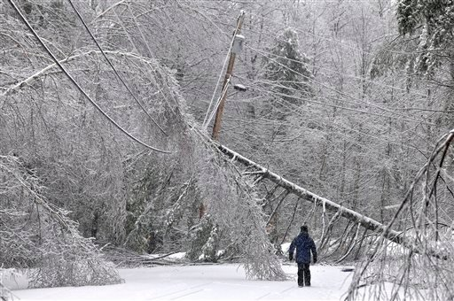 Karen Gibbs walks through a labyrinth of icy broken trees and downed power lines to her home on Maplehurst Drive in Belgrade, Maine on Thursday, Dec. 26, 2013.