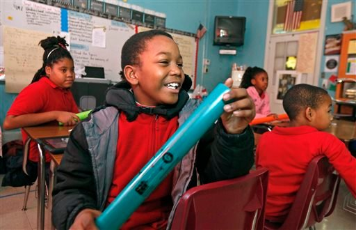 In this Dec. 16, 2018 photograph, fourth grader Jimmarious Frazier laughs at one of his classmates' inspired blues song at Tunica Elementary School in Tunica, Miss.