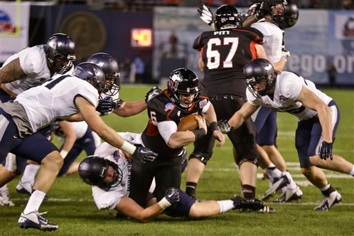 Northern Illinois quarterback Jordan Lynch plows his way through the Utah State defenders while stretching to get a first down at the 1-yard line during the first half of the Poinsettia Bowl NCAA college football game Thursday, Dec. 26, 2013, in San Diego