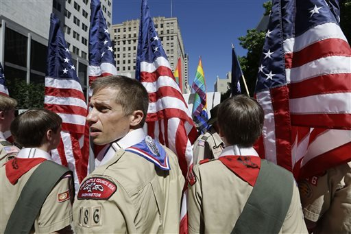 In this June 30, 2013 file photo, Boy Scouts from the Chief Seattle Council carry U.S. flags as they prepare to march in the Gay Pride Parade in downtown Seattle.