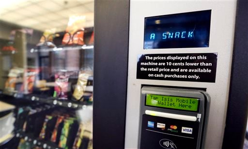 In this Dec. 23, 2013 photo, a vending machine advertises snacks on a small screen on the machine in Seattle.