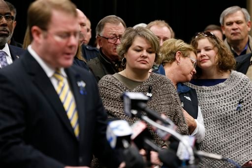 Stauffer Presser, center, reacts on Sunday, Dec. 29, 2013, as FBI Special Agent in Charge Danile McMullen announces they believe the bank robber who killed her husband, Sgt. Gale Stuaffer on Monday, was killed attempting another bank robbery in Phoniex.