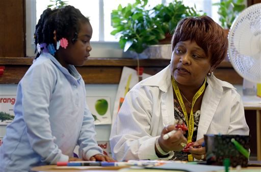 In this photo taken Wednesday, Nov. 13, 2013, Elmira Warren talks with Camil Douthit, 5, a student in Warren's pre-school class at Clay Elementary Community Education school in St. Louis.