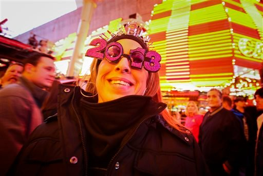 Monday, Dec. 31, 2012 file photo, Carmen Zepeda of Corpus Christi, Texas show off her 2013 New Year's Eve glasses at the Fremont Street Experience Downtown Countdown in Las Vegas.(AP Photo/Las Vegas Review-Journal, Jeff Scheid, File)