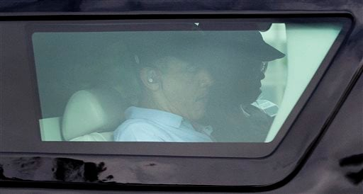 President Barack Obama is seen through the window of his motorcade vehicle as he is driven through the Kailua, Hawaii, neighborhood where he is spending his annual holiday vacation with his family, Monday, Dec. 30, 2013. (AP)
