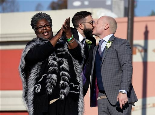 Aubrey Loots, right, and Danny Leclair, the first gay couple to be married aboard a float in the Tournament of Roses, kiss after being wed.(AP Photo/Reed Saxon)