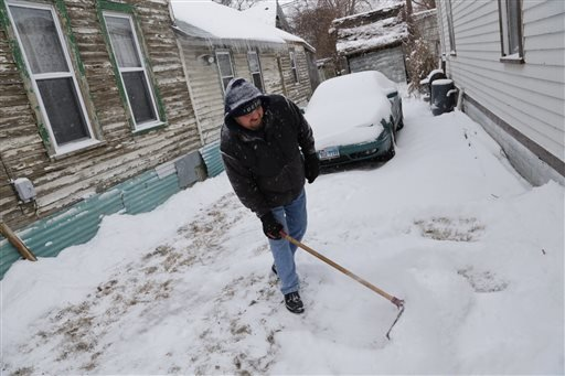 erry Gerardo Lopez shovels snow in his driveway on Roosevelt in Detroit on Wednesday, Jan. 1, 2014 as Detroit residents gear up for snow fall predicted to hit the area. (AP Photo/Detroit Free Press, Ryan Garza)