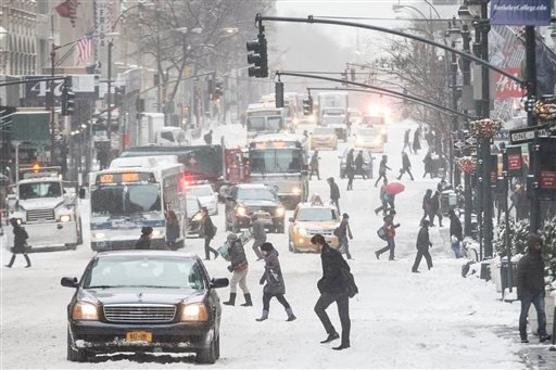Pedestrians brave wind and snow as they cross Fifth Avenue, Friday, Jan. 3, 2014, in New York.(AP Photo/John Minchillo)