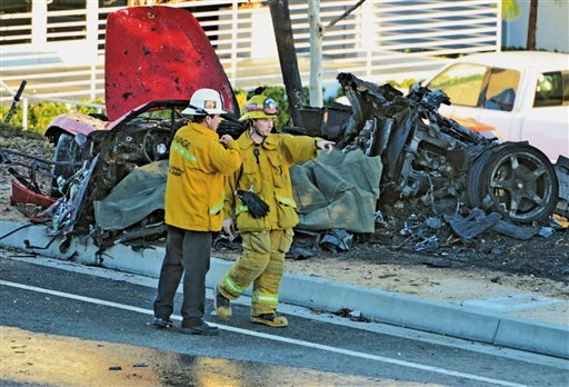 FILE - In this Nov. 30, 2013, file photo, sheriff's deputies work near the wreckage of a Porsche that crashed into a light pole on Hercules Street near Kelly Johnson Parkway in Valencia, Calif. (AP)