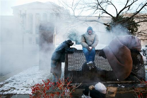 Four homeless men warm themselves on a steam grate by the Federal Trade Commission, blocks from the Capitol, during frigid temperatures in Washington, Saturday, January 4, 2014.