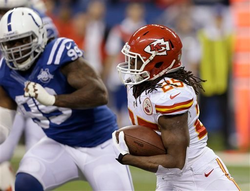 Kansas City Chiefs running back Jamaal Charles (25) runs as Indianapolis Colts defensive end Ricky Jean Francois (99) moves in during the first half of an NFL wild-card playoff football game Saturday, Jan. 4, 2014, in Indianapolis.