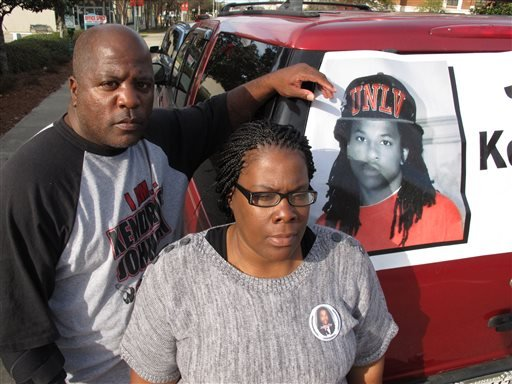 Kenneth and Jacquelyn Johnson stand next to a banner on their SUV showing their late son, Kendrick Johnson, on Dec. 13, 2013, in Valdosta, Ga.
