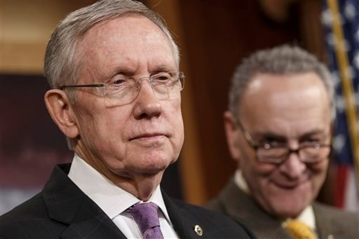 In this Dec. 19, 2013, file photo, Senate Majority Leader Harry Reid of Nev., left, accompanied by Sen. Charles Schumer, D-N.Y., listens during a news conference on Capitol Hill in Washington.