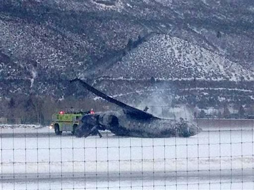 Emergency crews respond as a small plane lies on a runway at Aspen Airport in western Colorado after it crashed upon landing Sunday, Jan. 5, 2014.