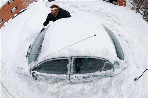 In an image made with a fisheye lens, Marguerite Johnston uncovers her car in Grosse Pointe, Mich., Monday, Jan. 6, 2014.