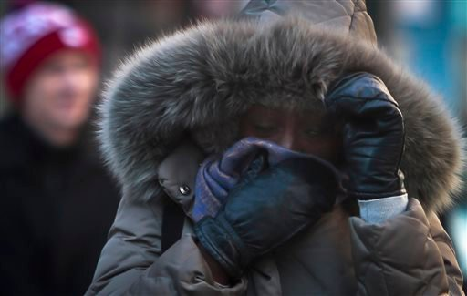 A New York City pedestrian covers up against single-digit temperatures, Tuesday, Jan. 7, 2014. The high is expected to be 10 degrees. But wind chills will make it feel more like minus 10. (AP Photo/Bebeto Matthews)