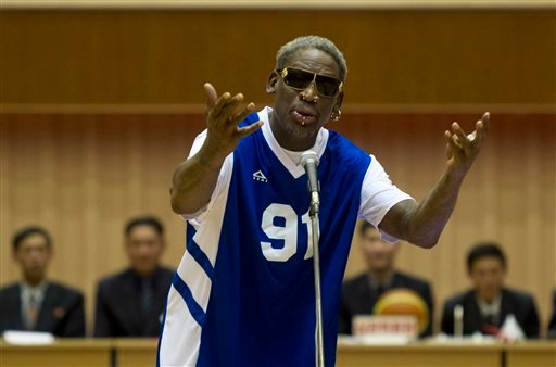 Dennis Rodman sings Happy Birthday to North Korean leader Kim Jong Un, seated above in the stands, before an exhibition basketball game at an indoor stadium in Pyongyang, North Korea on Wednesday, Jan. 8, 2014. (AP Photo/Kim Kwang Hyon)