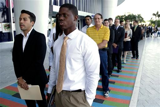 In this Wednesday, Oct. 23, 2013 file photo, Luis Mendez, 23, left, and Maurice Mike, 23, wait in line at a job fair held by the Miami Marlins, at Marlins Park in Miami.