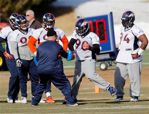 Denver Broncos defensive end Shaun Phillips (90) works on drills as other defensive linemen look on during practice for the football team's NFL playoff game against the San Diego Chargers at the Broncos training facility in Englewood, Colo., on Thursday.