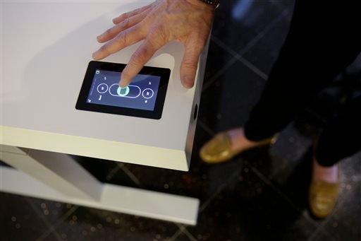 Jennifer McNally, a head of marketing at Stir, demonstrates on the Kinetic Desk at the International Consumer Electronics Show on Wednesday, Jan. 8, 2014, in Las Vegas. (AP)