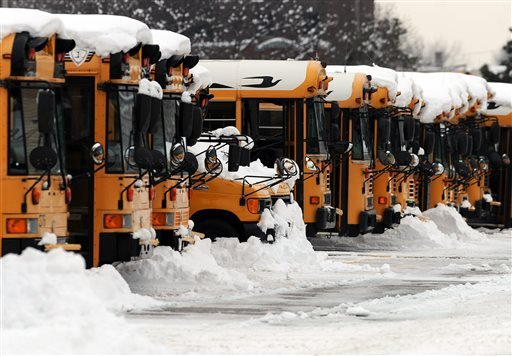 Indianapolis Public School buses sit covered in snow at a depot, Thursday, Jan. 9, 2014 in Indianapolis. (AP)