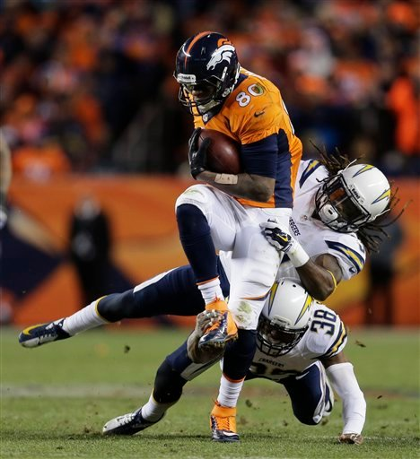 Denver Broncos tight end Julius Thomas (80) is pulled down by San Diego Chargers defensive back Jahleel Addae (37) and San Diego Chargers strong safety Marcus Gilchrist (38) in the fourth quarter of an NFL AFC division playoff football game..