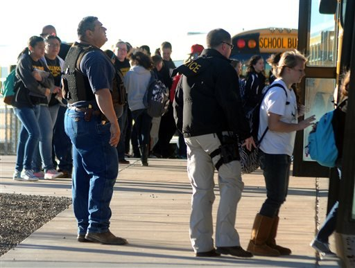 Authorities stand guard as students are escorted from Berrendo Middle School after a shooting, Tuesday, Jan. 14, 2014, in Roswell, N.M. (AP)