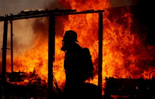 This Tuesday Jan. 14, 2014 photo shows a Riverside County firefighter walking past a fully engulfed burning home in Jurupa Valley, Calif. (AP)