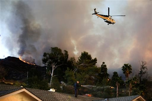 A helicopter carrying water flies over the residential area as a man sprays water on his home on Thursday, Jan. 16, 2014, in Azusa, Calif. (AP)