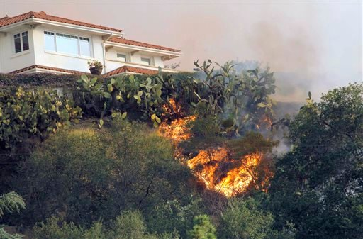 A fast moving wildfire makes it way up a hill towards a house in the hills just north of the San Gabriel Valley community of Glendora, Calif. on Thursday, Jan 16, 2014. (AP)