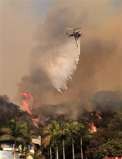 A firefighting helicopter makes a water drop over homes in Glendora, Calif., as a wildfire burns in the hills just north of the San Gabriel Valley community on Thursday, Jan 16, 2014. (AP)