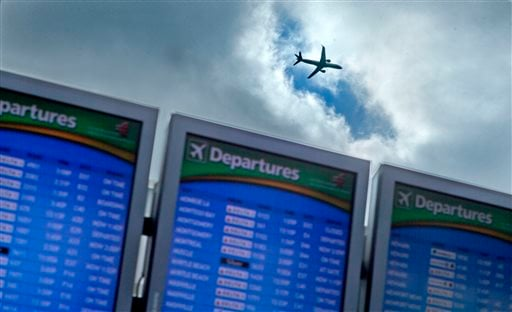 FILE - In this Wednesday, Nov. 27, 2013, file photo, a plane takes off over a departure board at Hartsfield-Jackson Airport, in Atlanta. (AP)