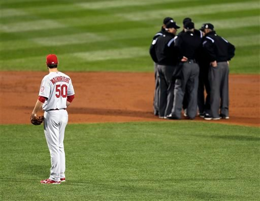 FILE - In this Oct. 23, 2013, file photo, St. Louis Cardinals starting pitcher Adam Wainwright watches as umpires discuss a ruling during the first inning of Game 1 of baseball's World Series against the Boston Red Sox in Boston. (AP)